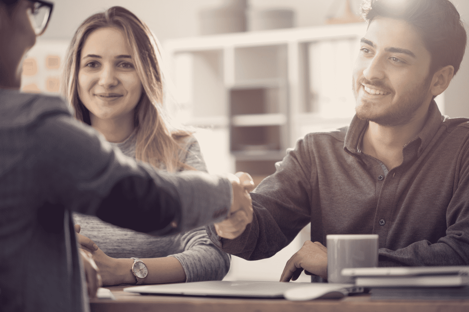 Employees shake hands at a table in an office