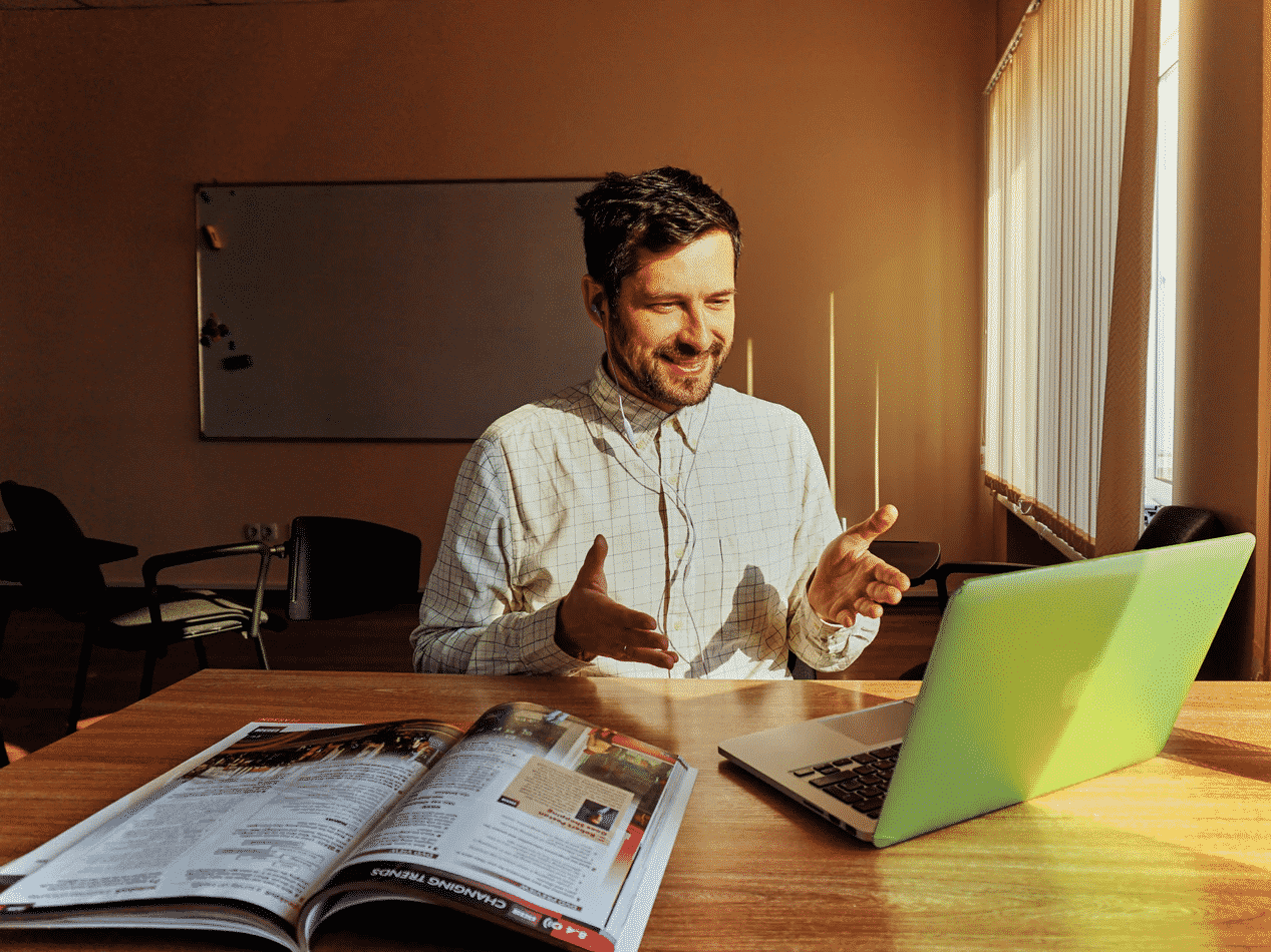 Man at desk with laptop and brochure