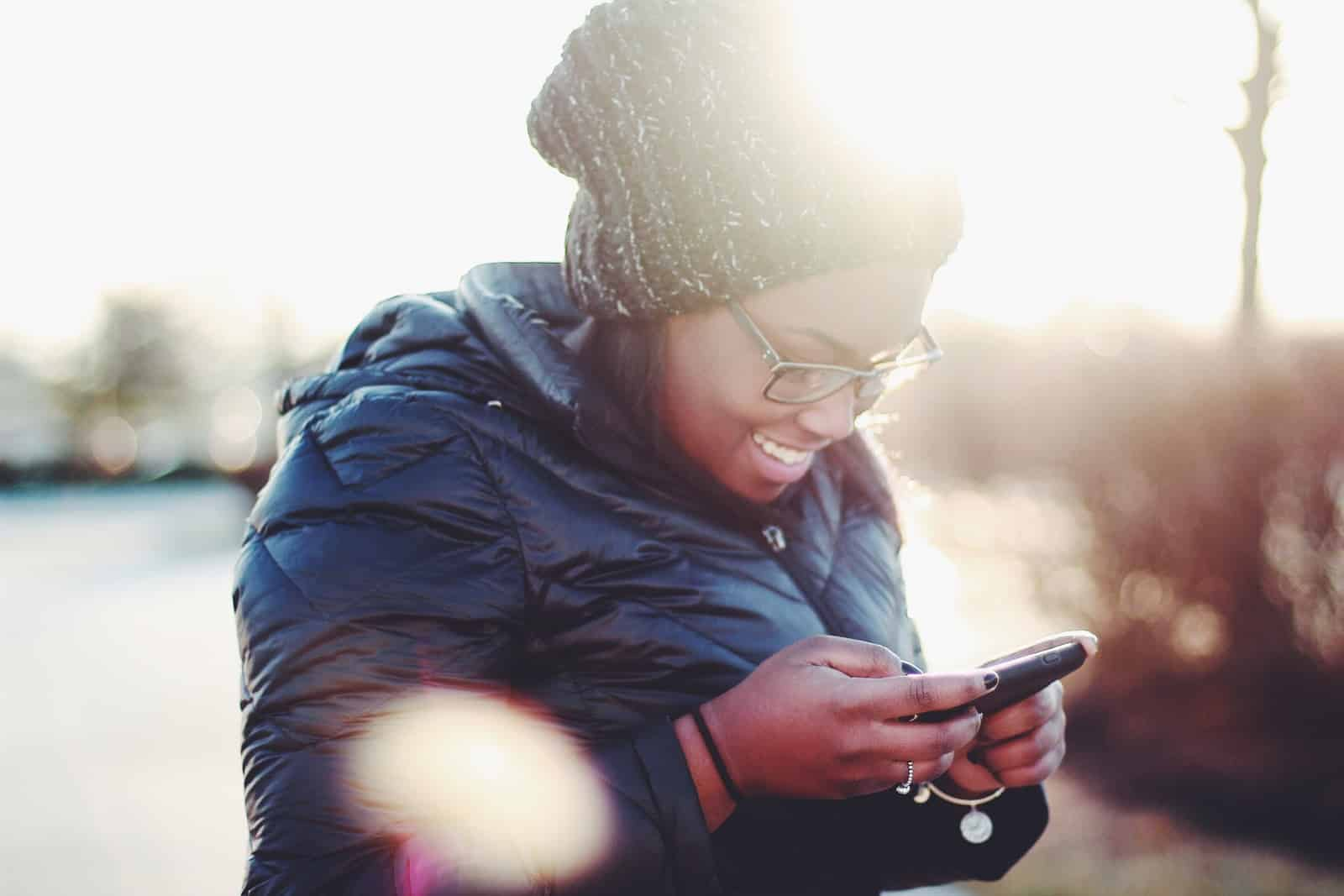 woman in coat and hat texting and smiling